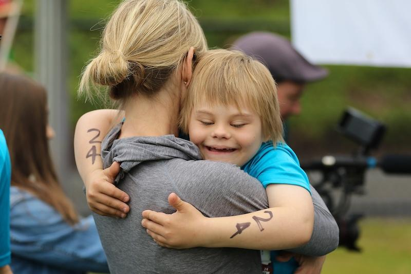 Woman and son hugging at triathlon event