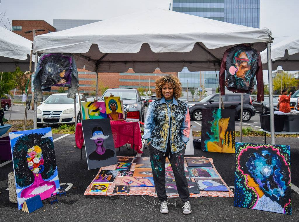Artist standing in front of artwork at The Bank