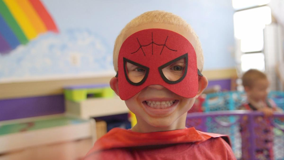 boy with red mask smiling
