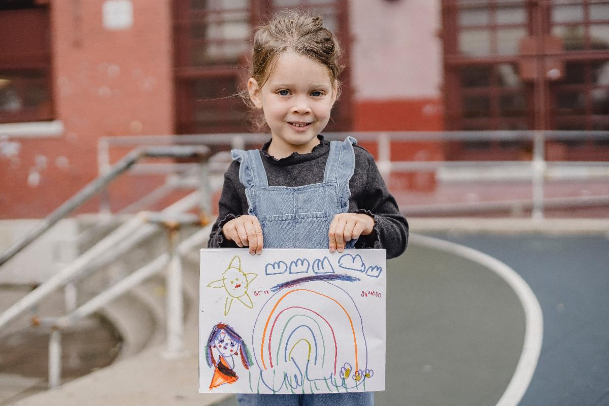 Image, child holding a drawing.