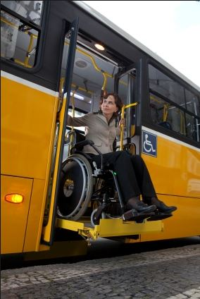 female wheelchair user using chair lift to exit a bus