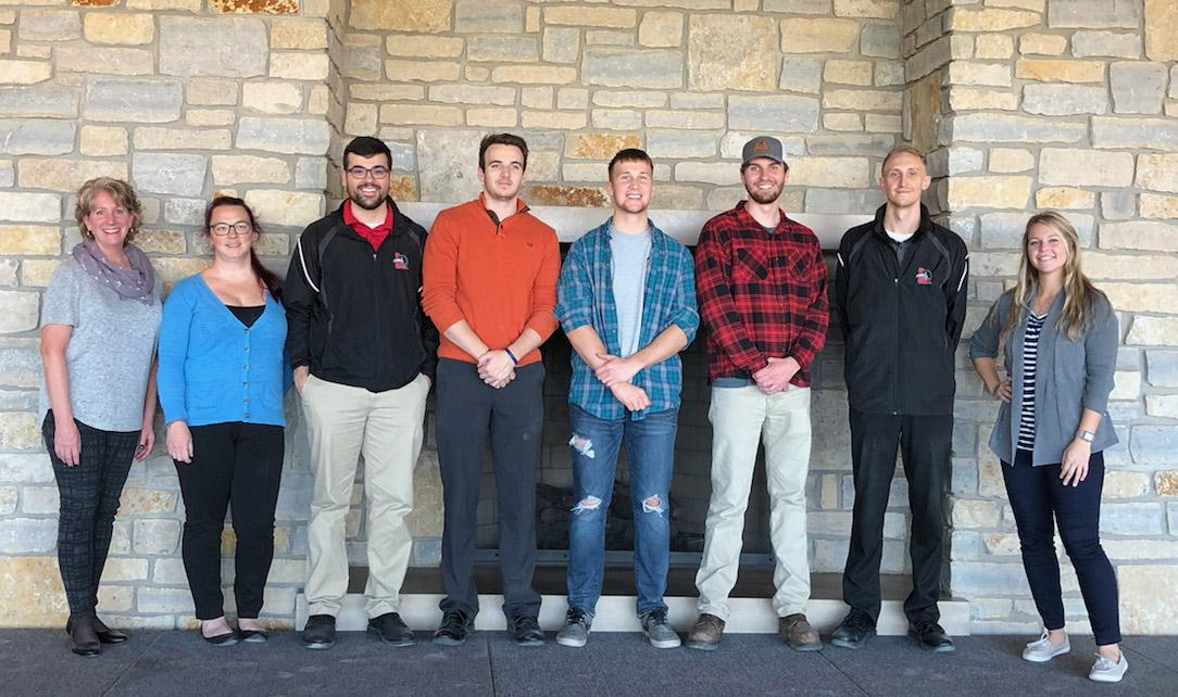 8 men and women standing in front of fireplace at Dow diamond_ the top four placing cornhole teams