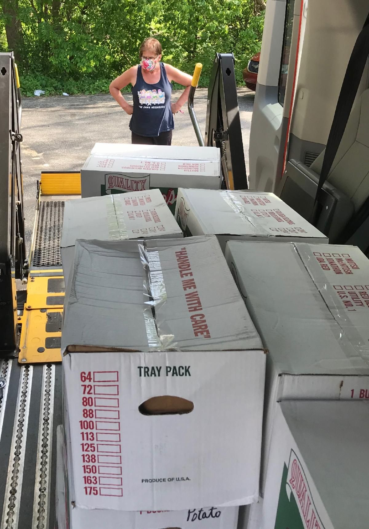 dnmm employee wearing mask prepares to unload boxes from van