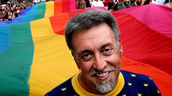 man standing infront of gay pride flag