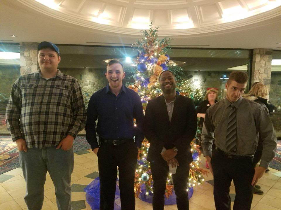 four men standing in front of christmas tree at holiday dance