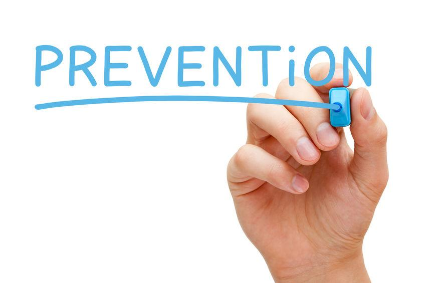 hand hold marker writing the word prevention in light blue