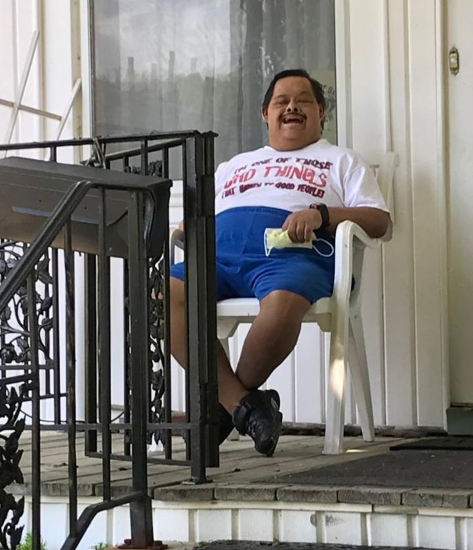 consumer smiling sitting on porch while food being delivered