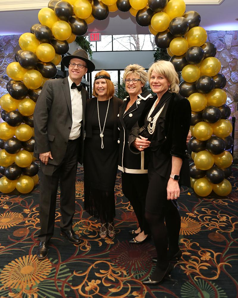 four people standing in front of gold and black balloon arch