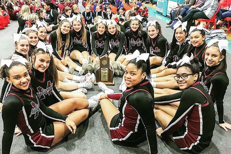 MNHHS cheer team sits on floor around Sectional Champion trophy