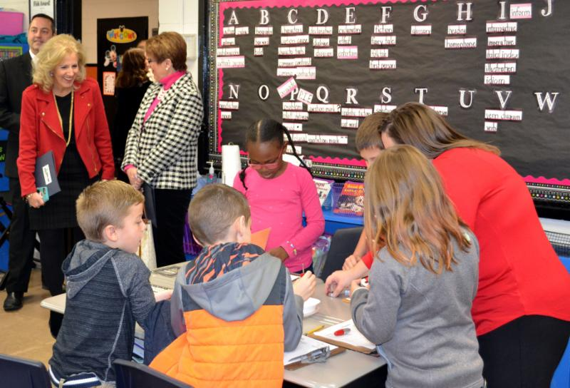Elementary students work together at desks_ with Superintendent Ashby and other administrators observing.
