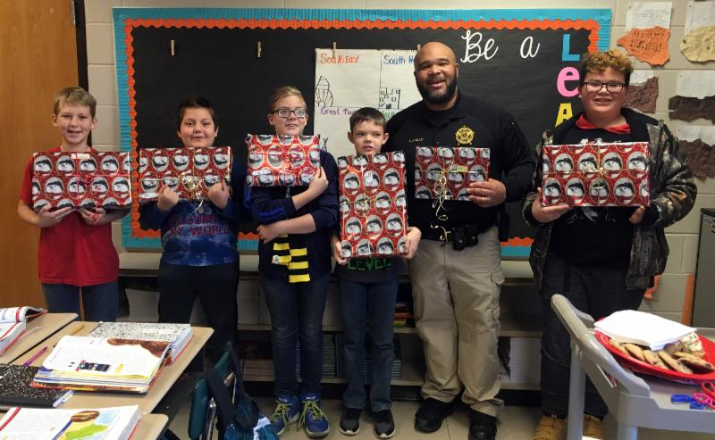 SRO LyDon Logan with five students holding wrapped gifts