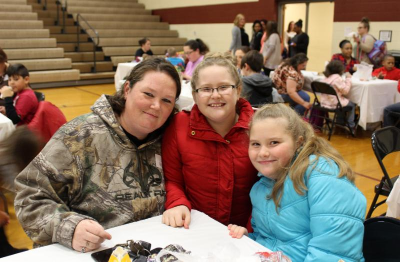 Mom with two daughters at table in Jesse Stuart gym