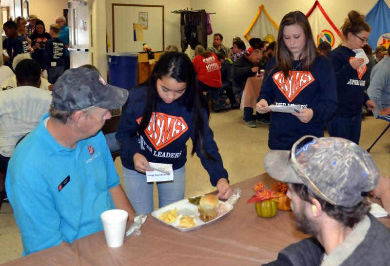 Student serves lunch to man