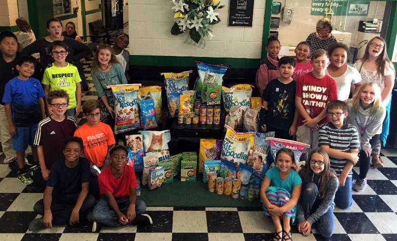 Grapevine students with items collected during cat food drive.