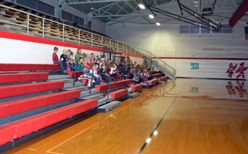 Class sits in two sections of the new lower red bleachers in the gym