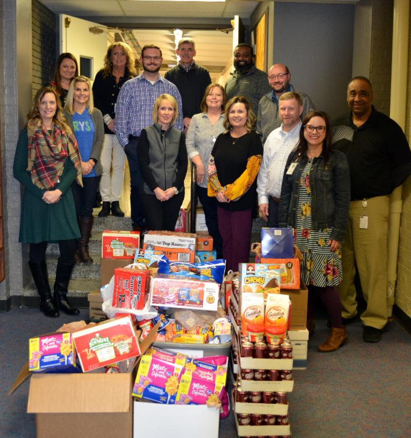 Group photo with 14 people and several boxes filled with individual food items.