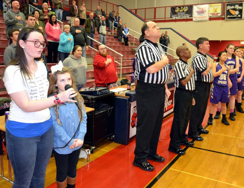 Two students sing National Anthem at basketball game