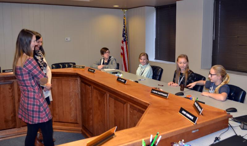 Four students sit at boardroom table_ talking to two employees.