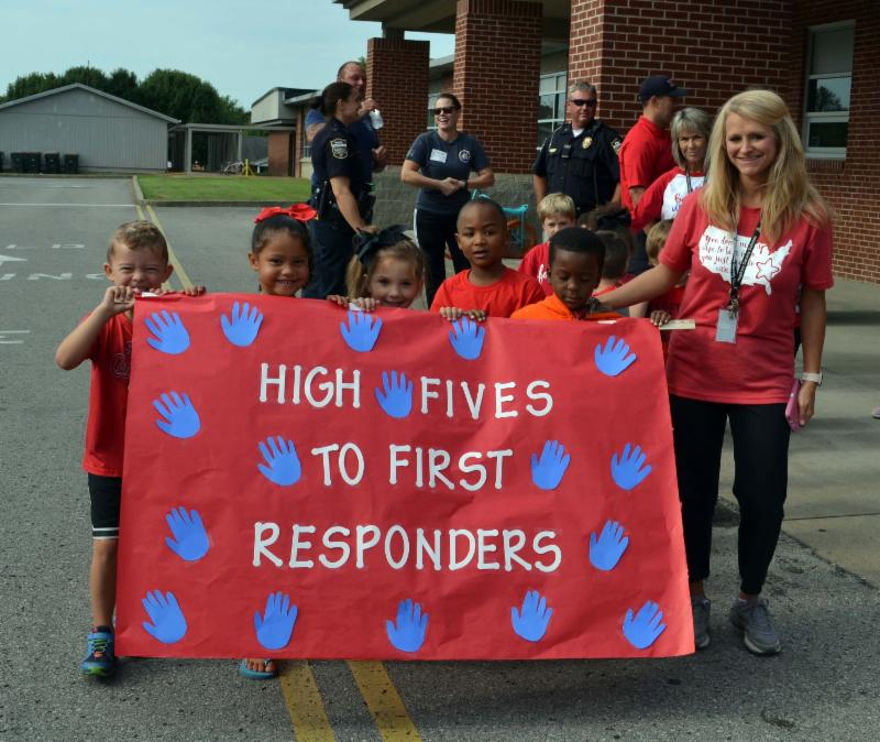 Five students adn teacher carry sign that says _High fives to first responders._