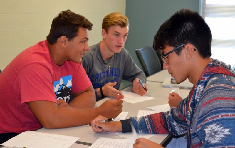 Three students work on group project at desk