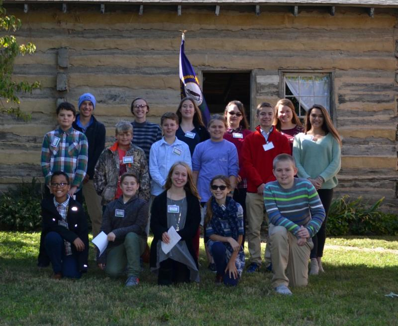 Group photo in front of log cabin