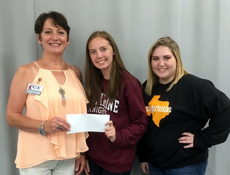 Tumbleweed manager and two students hold donation for hurricane relief.