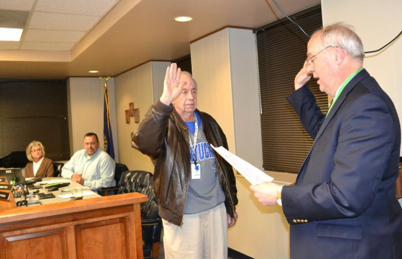 Board attorney Keith Cartwright administers oath of office to Bobby Fox