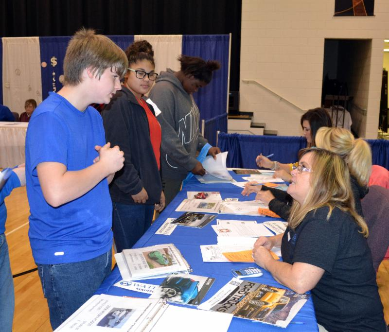 Students talk to volunteers about buying a car.