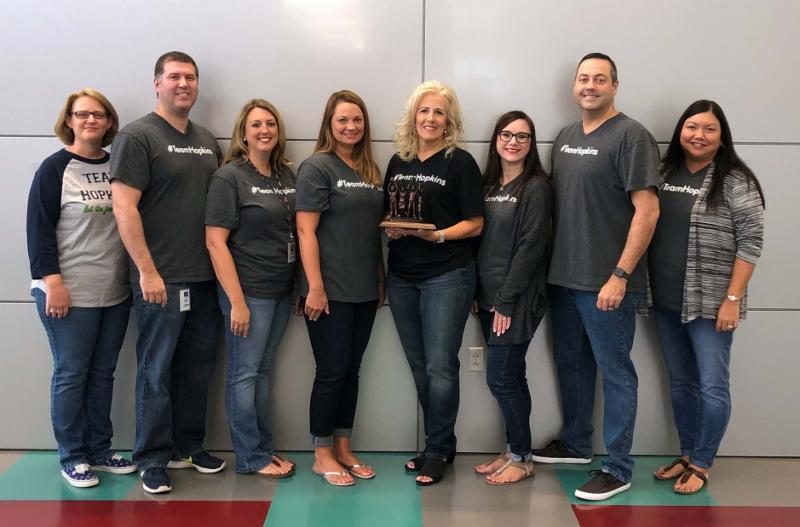 Superintendent Ashby_ holding the award_ poses with seven Central Office directors.