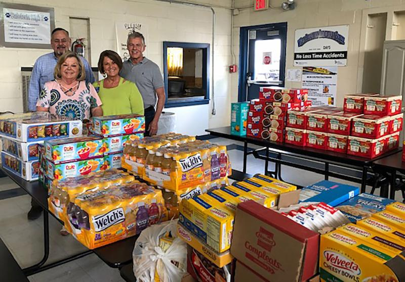 Four people with collection of food items