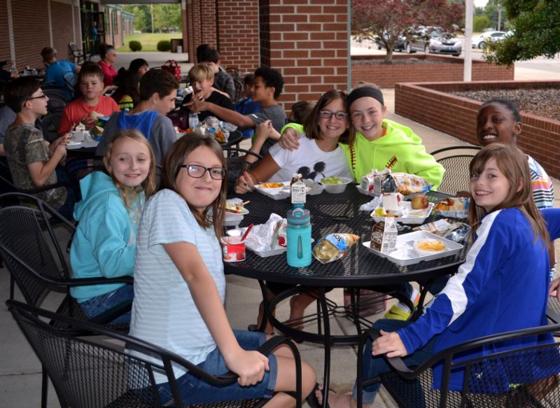 Six students eat lunch at patio table