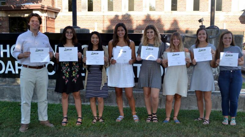 Eight high school students stand in a row with certificates