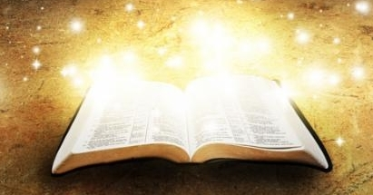 Open bible glowing with cross on the background