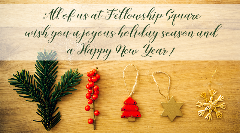 holiday ornaments on wood background with Happy Holiday message