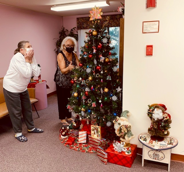 woman shows surprise while admiring christmas tree while second woman gives a thumbs up