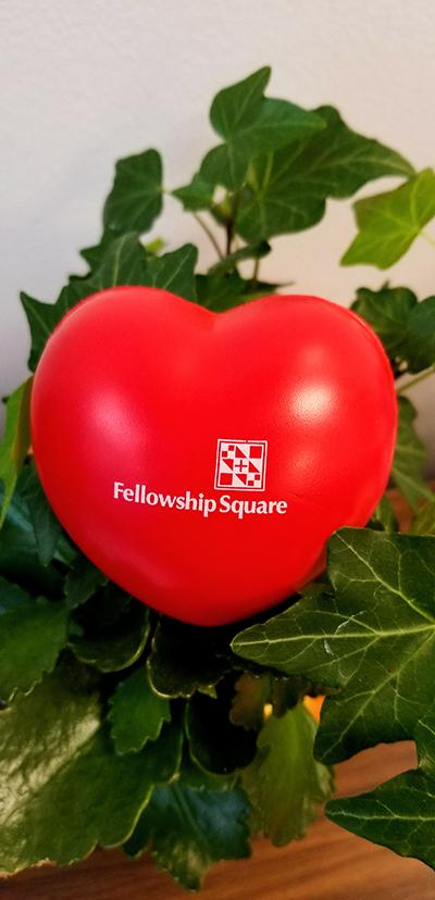 Red heart with Fellowship Square logo set in greenery