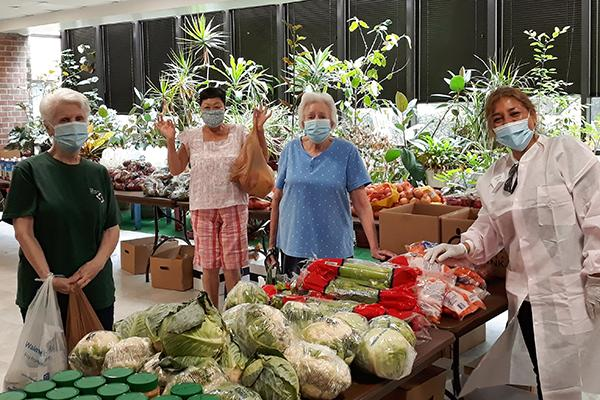 4 female masked volunteers posing by a table piled with fresh vegetables