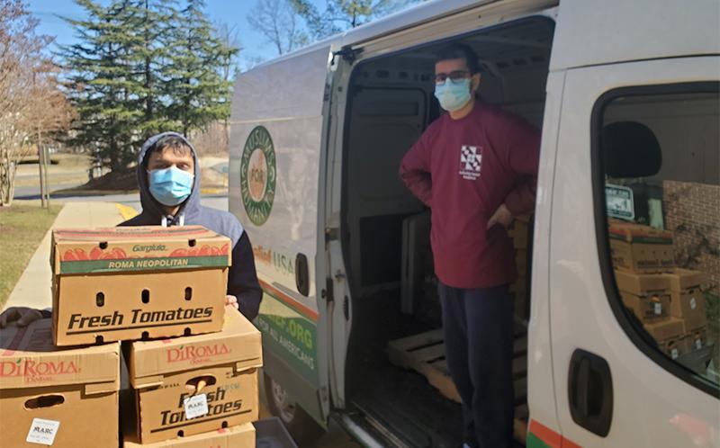 2 men loading boxes onto a van