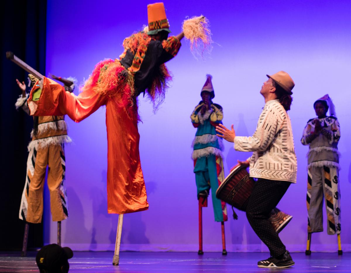 masquerading stilt dancer in orange and black costume hopping on one stilt in front of a person with brown skin playing a drum wearing a white shirt, black pants, and a brown hat