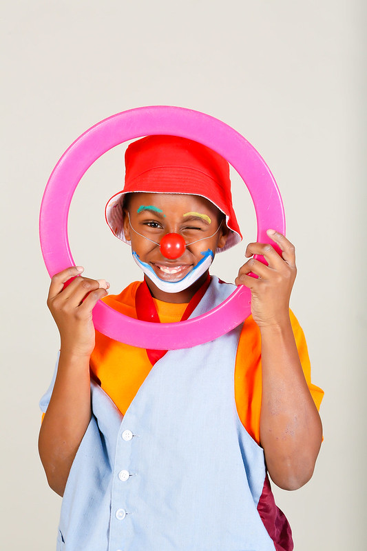 boy with brown skin wearing a blue vest and orange shirt with a red clown nose and red hat is holding a pink ring in front of face smiling and winking