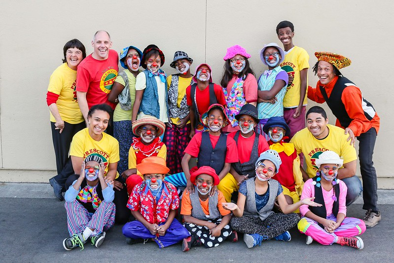 group photo of three rows of children with Black and Brown skin wearing colorful costumes and clown make up and red noses.
