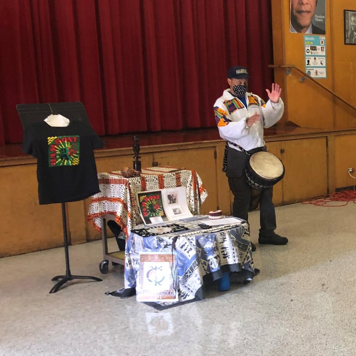 adult Black man wearing black pants and a white shirt with colorful patterned patches plays a drum next to an alter with displays of African symbols and photos and objects