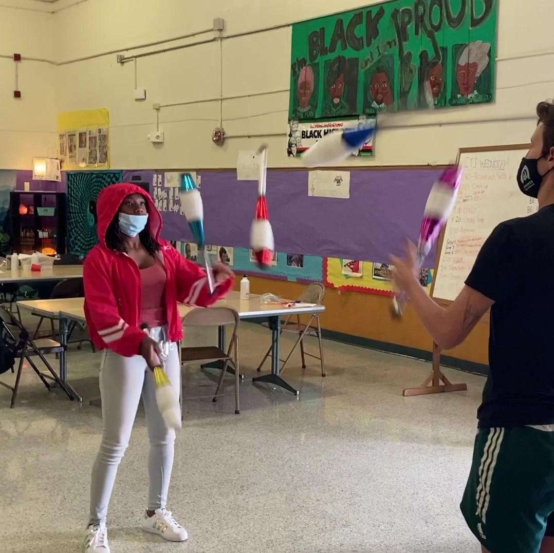 A girl with brown skin wearing a mask and red sweatshirt is passing juggling clubs with their coach