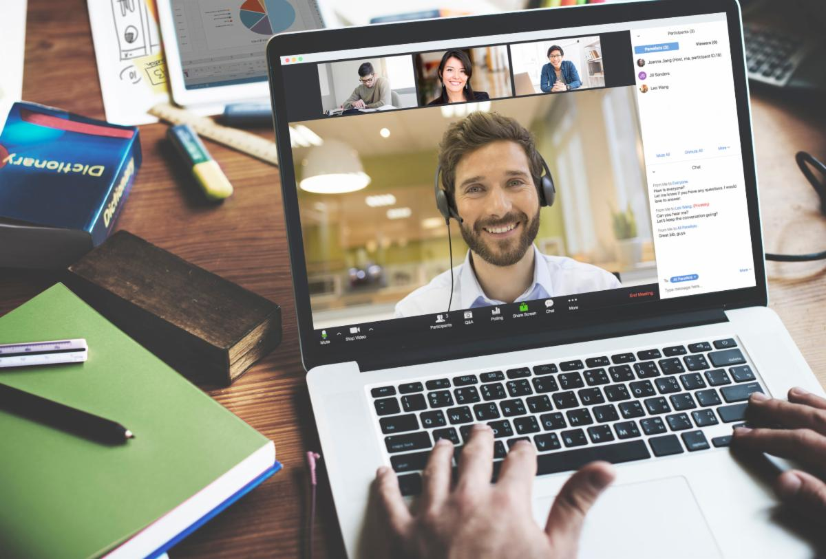 zoom interface on laptop with user video conferencing with 3 others