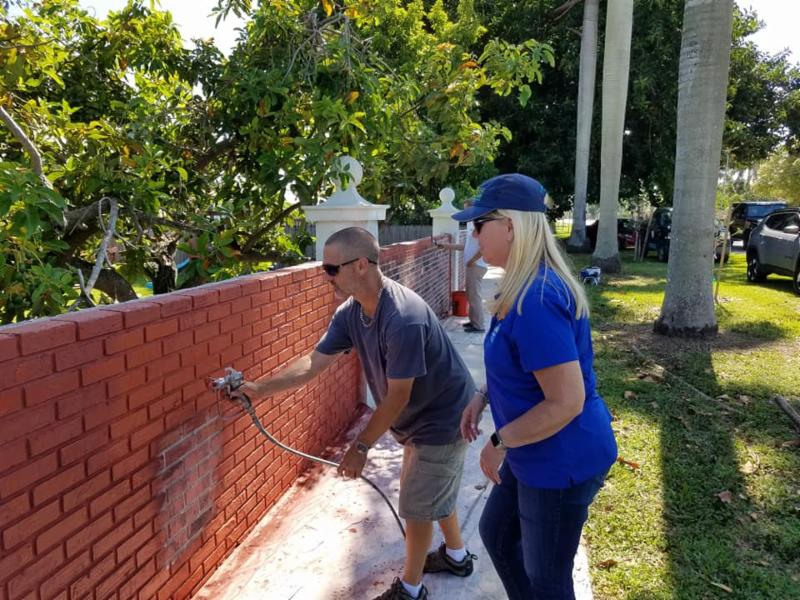 Mayor Cunningham and volunteer paint the wall