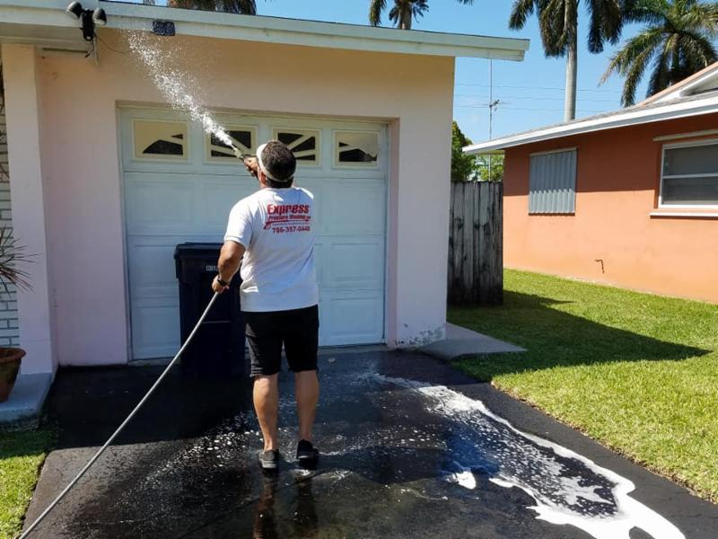 Photo of volunteer pressure washing the exterior of a home.