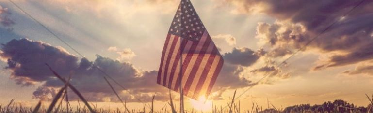 Photo of an American flag with sunrise in the background.