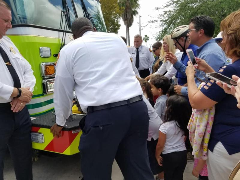 Photo of firefighters, Mayor and Council, and others putting their hands on a fire truck and pushing it into it's bay at Station number fifty