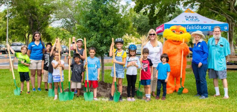 Photo of young children and Mayor Cunningham, Councilmember Matson holding shovels about to plant a tree.