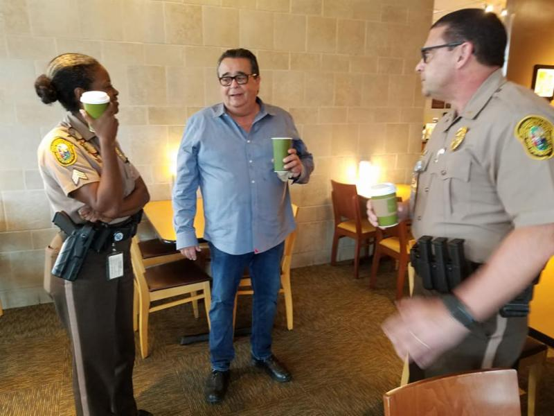 Two members of Palmetto Bay's Policing Unit chat with a resident at coffee with a cop on April 10, 2019
